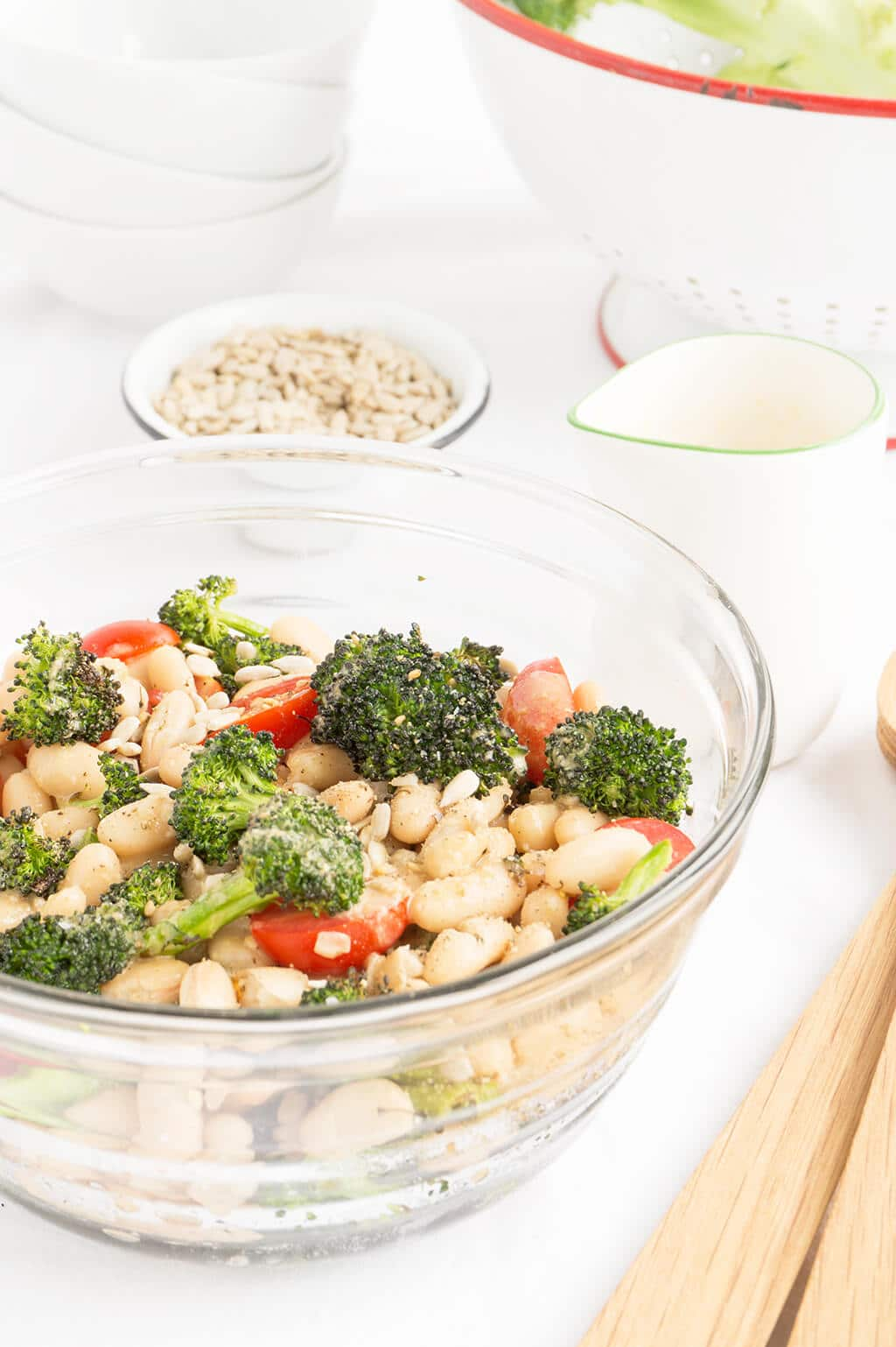 This Roasted Broccoli Salad can be served warm or cold. Tomatoes, cannellini beans, toasted sunflower seeds + Sesame-Ginger Dressing - it's healthy & quick! HEALTHY   VEGETARIAN   BROCCOLI   Recipe at OatandSesame.com