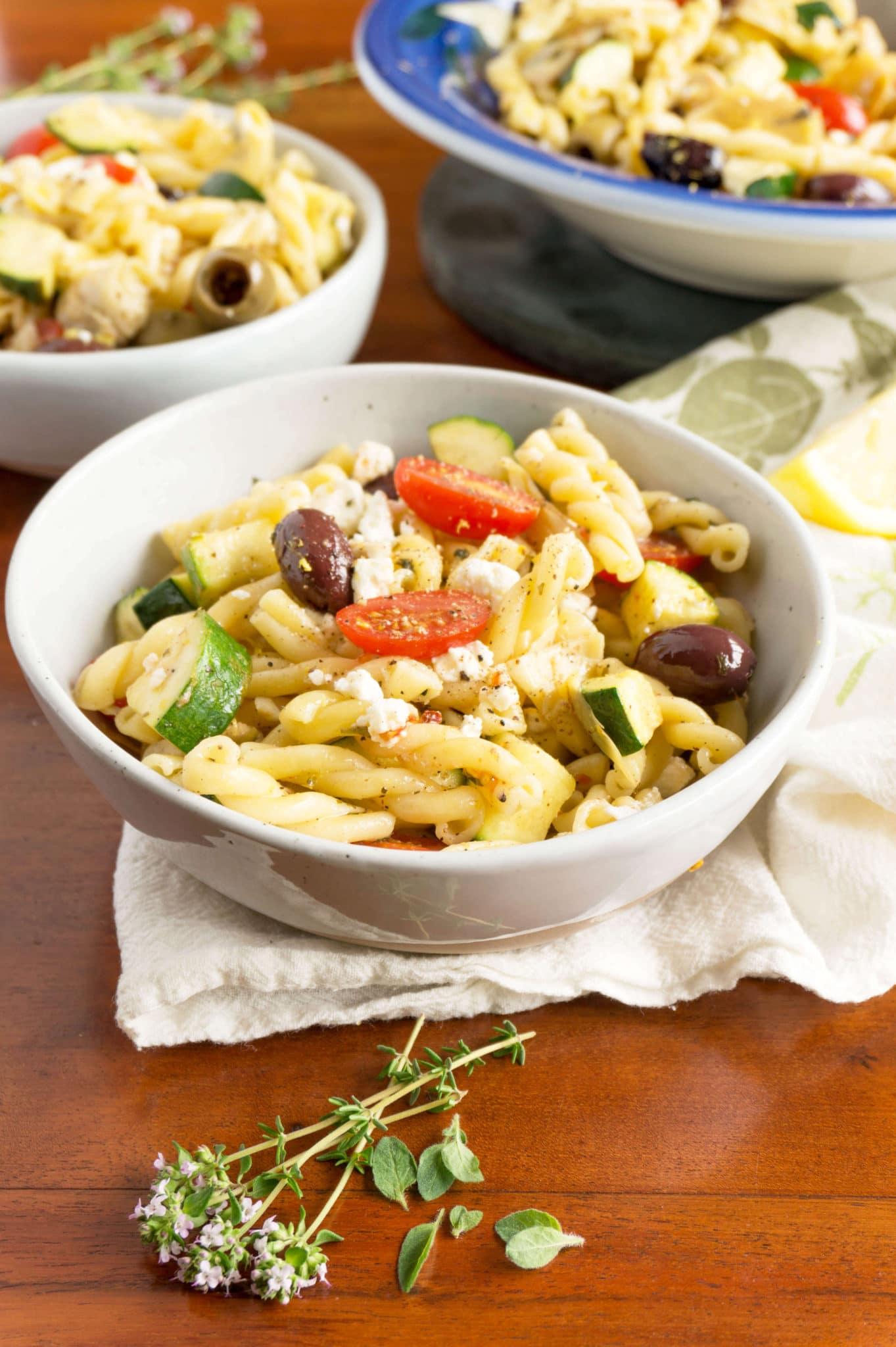 Lemon, Garlic + Herbs dress this one-pot Greek Pasta Salad with creamy French feta cheese, olives, artichokes and zucchini! | PASTA | ZUCCHINI | VEGETARIAN | GREEK | Recipe at OatandSesame.com