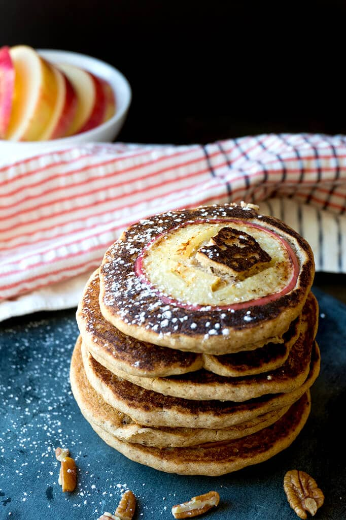 These fluffy Whole Grain Apple Pancakes use APPLE CIDER to add extra apple flavor. Dairy free and whole grain, these are more than just your typical sweetened pancake. Drizzled with an apple peanut butter sauce to add a little plant based protein makes them hearty and low in sugar. The way breakfast should be! | BREAKFAST | DAIRY FREE | PANCAKES | WHOLE GRAIN | APPLES | Recipe at OatandSesame.com