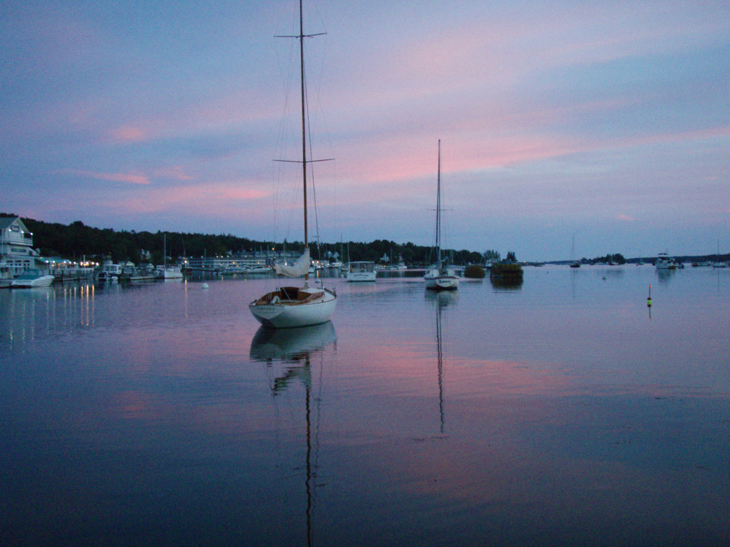Boat in harbor with pink sunset