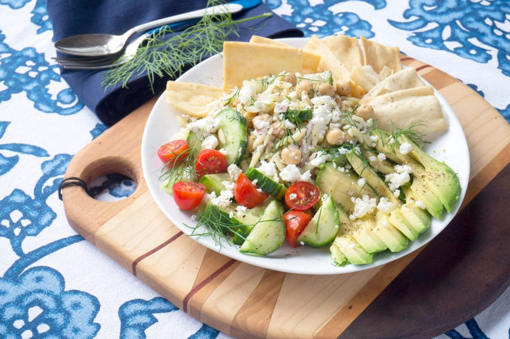 Mediterranean Orzo Salad on plate with blue tablecloth