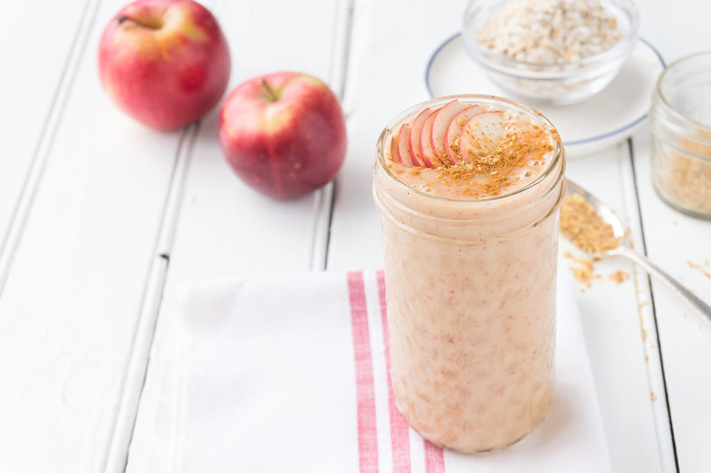 An Apple Oat Smoothie in a glass with apples in the background