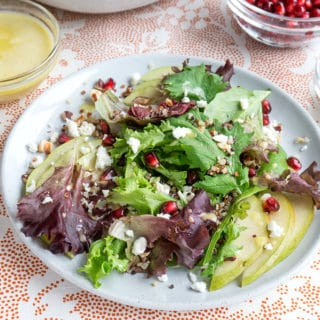 salad on a serving plate with cup of dressing and cup of pomegranate kernels