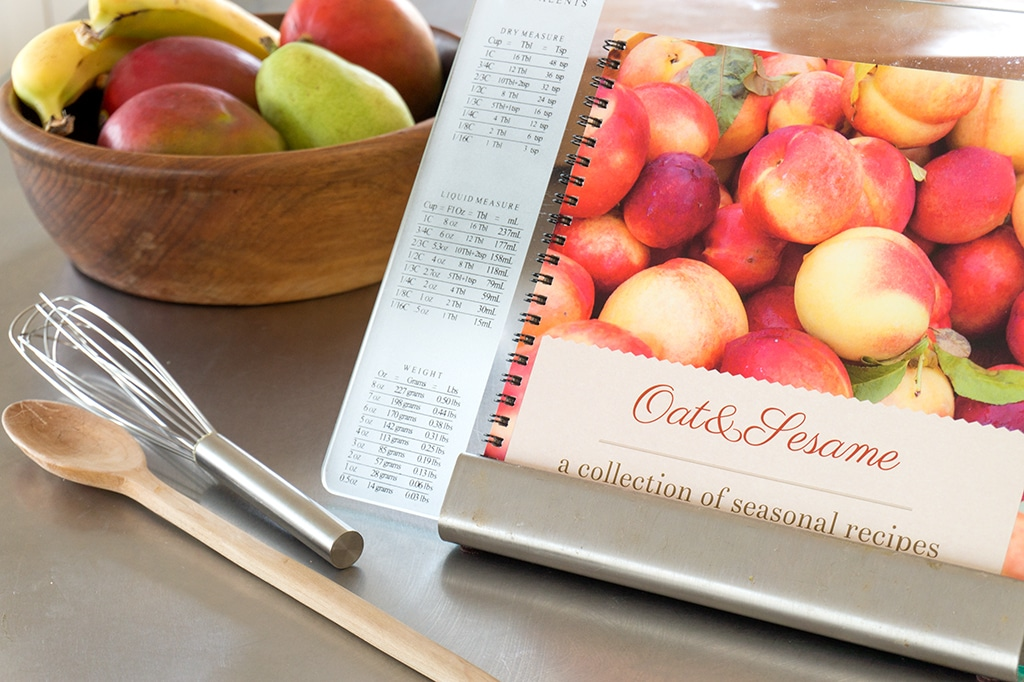 cookbook on glass stand with bowl of fruit