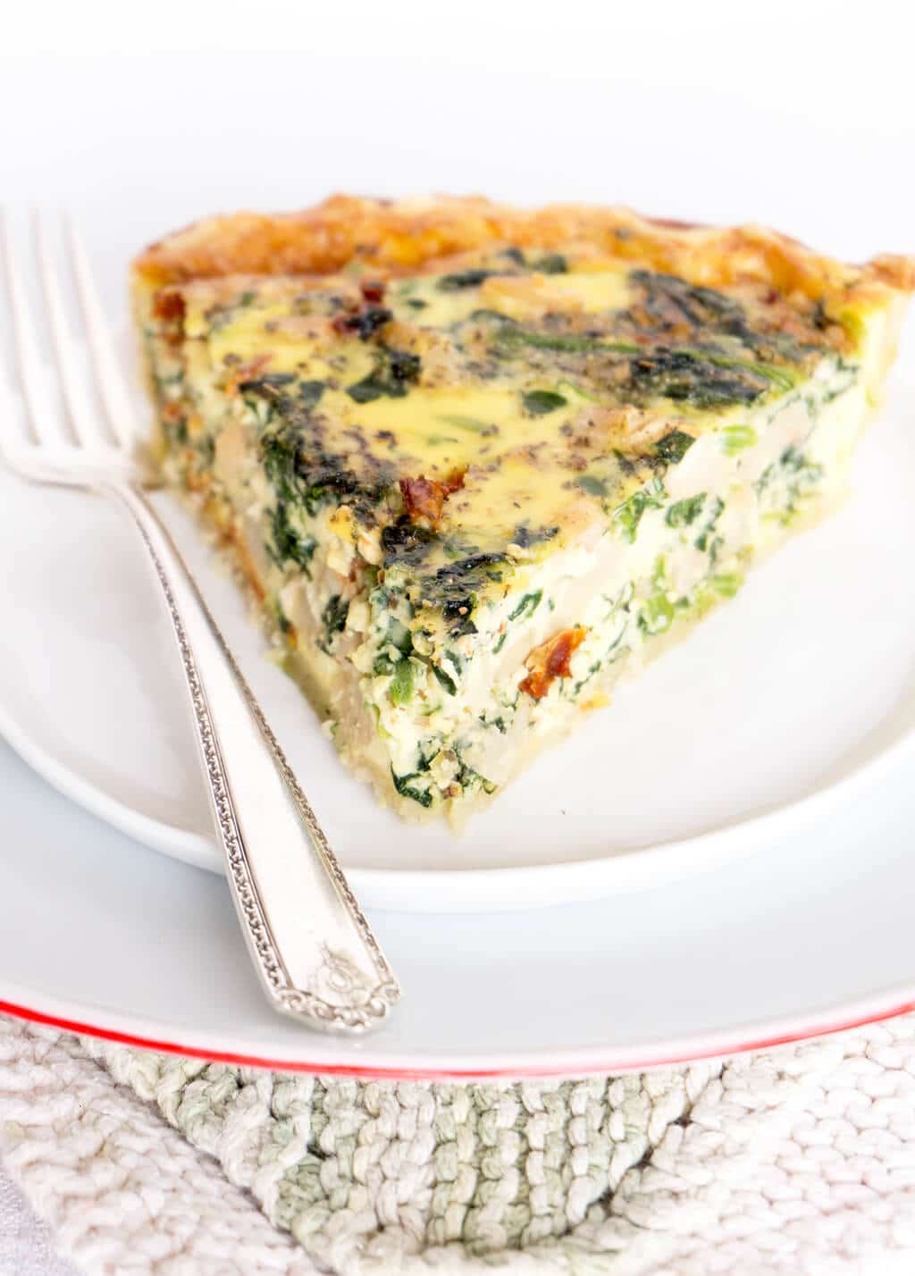 Spinach, White Bean & Sun Dried Tomato Quiche close up on plate