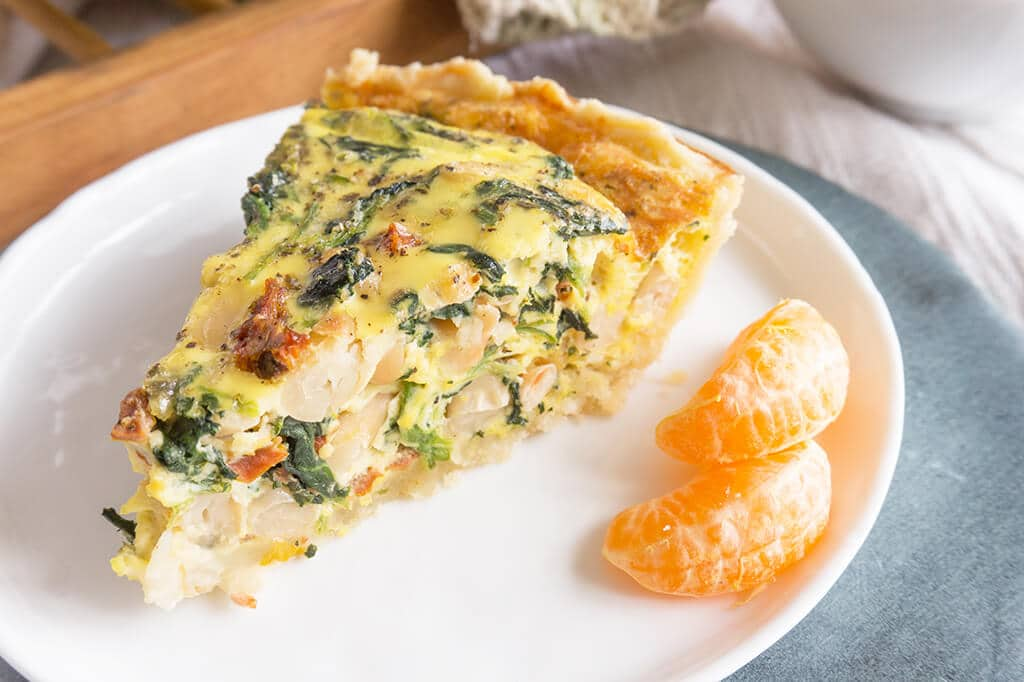 Spinach, White Bean & Sun Dried Tomato Quiche - slice on plate with tangerines