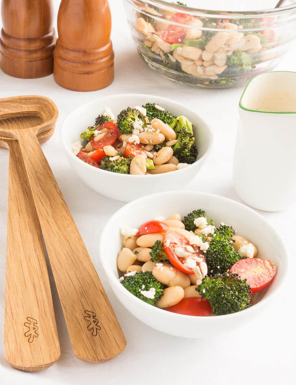 Roasted Broccoli Salad in bowls with serving utensils