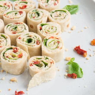 Sun Dried Tomato + Basil Pin Wheels lined up on a plate