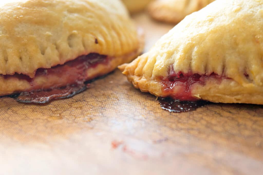 cranberry sauce dribbling out the sides of the baked handpies