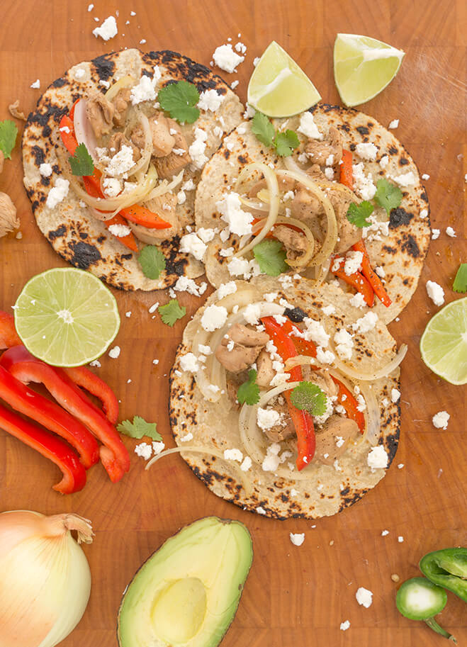 Marinated chicken tacos vertical on cutting board