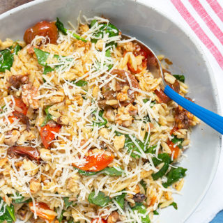 Spicy Roasted Tomato Pasta Salad is the most delicious way to use cherry tomatoes - especially if they're homegrown! Orzo pasta tossed with sweet roasted tomatoes, fresh spinach, toasted walnuts then seasoned with lemon and harissa to create a spicy and sweet pasta salad with a nutty crunch. | #PASTA | #SALAD | #TOMATOES | #VEGETARIAN | #Recipes at OatandSesame.com
