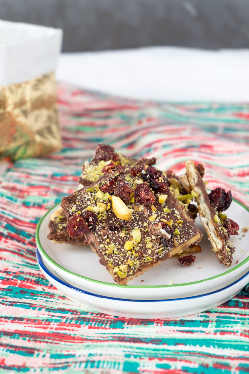Vertical image of saltine toffee showing pistachios and dried cherries