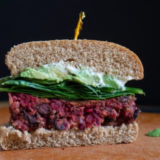 Red Beet Burger on bun sliced in half with toothpick on top