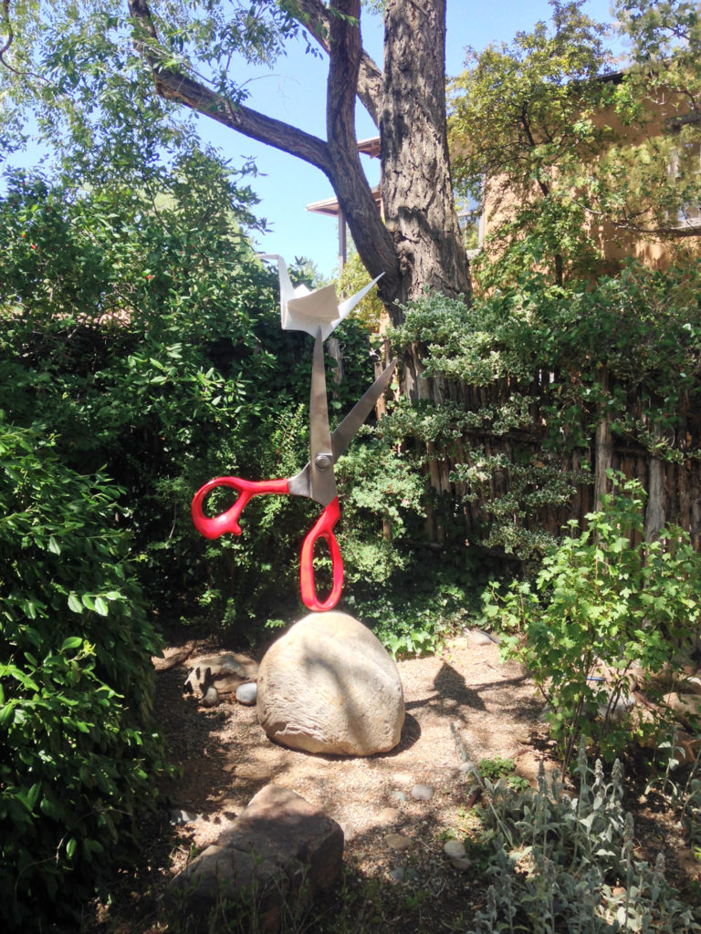 garden sculpture, scissors with red handle on rock and paper crane