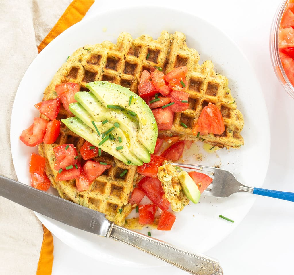 healthy waffle with tomatoes and sliced avocado on a white plate with knife and fork