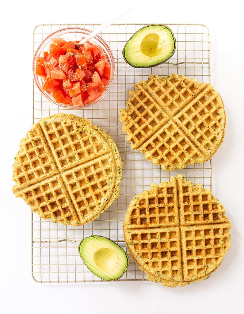 Healthy Waffles on cooling rack with a bowl of diced tomatoes and an avocado