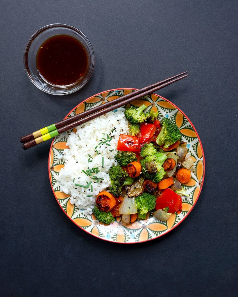 easy vegetable stir fry on plate with stir fry sauce in small glass bowl