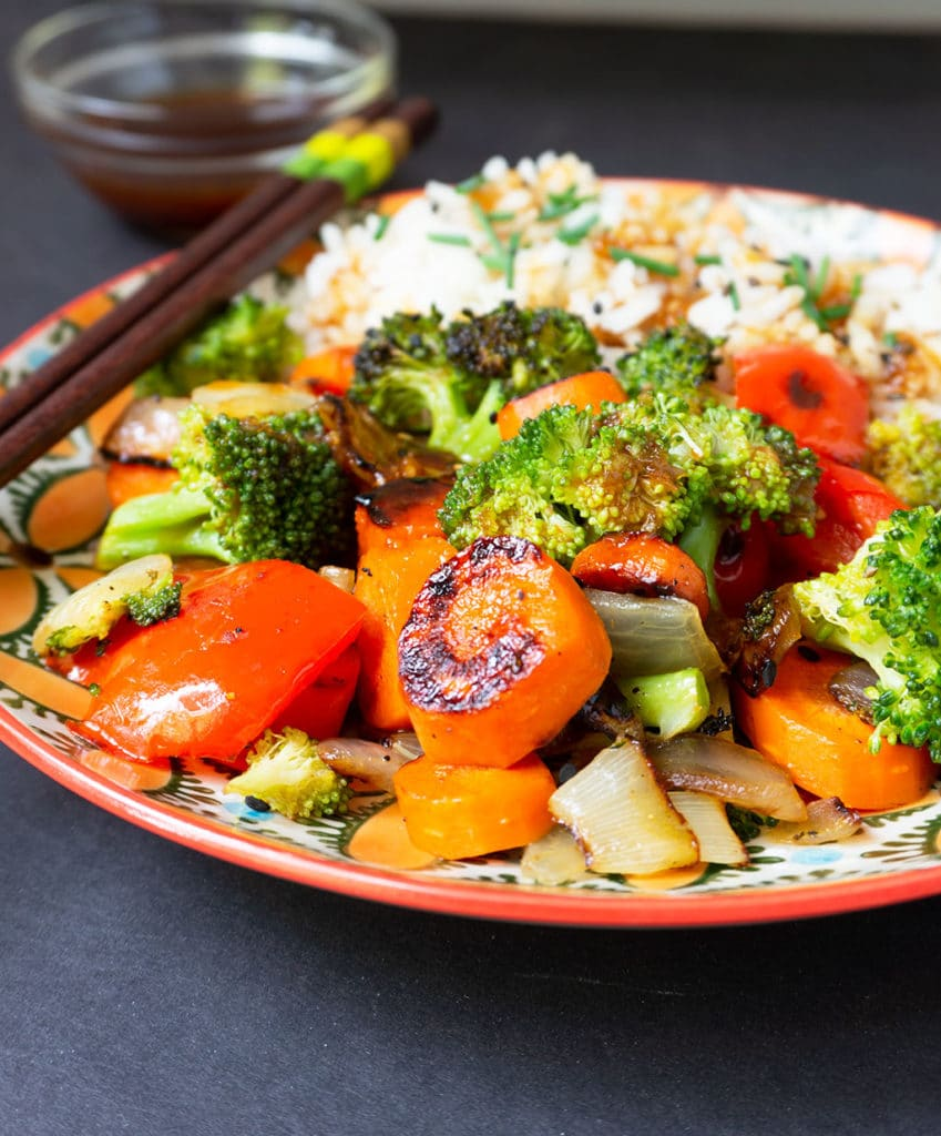 close up of vegetable stir fry with chopsticks
