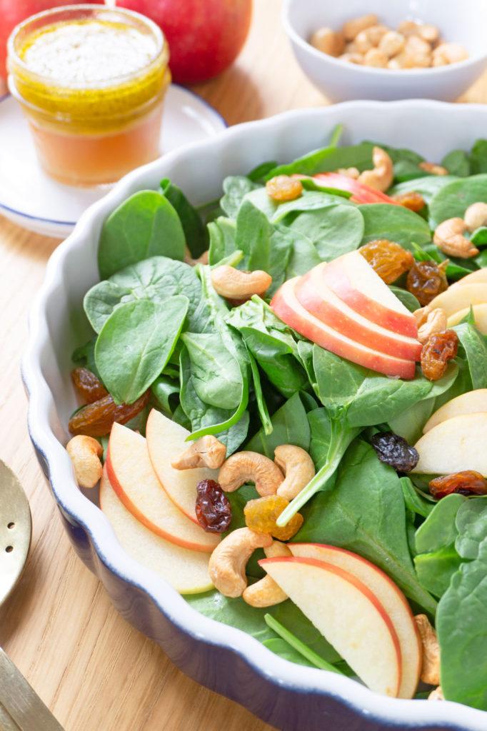 A BRIGHT AND CRISP APPLE SALAD! Packed with spinach, this Apple-Cashew Spinach Salad is dressed with a tangy apple cider vinaigrette and mixed with creamy cashews and sweet apple and raisins. | #AppleRecipes | #AppleSalad | #SaladIdeas | #VegetarianRecipes | #HealthyRecipes at OatandSesame.com #oatandsesame