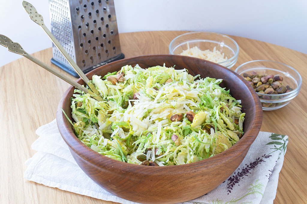 shaved brussels sprouts salad in a wooden bowl with gold utensils