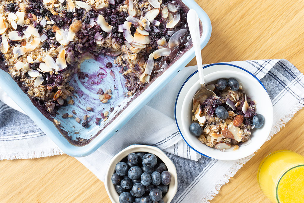 baked oatmeal in pan with bowl of blueberries on the side