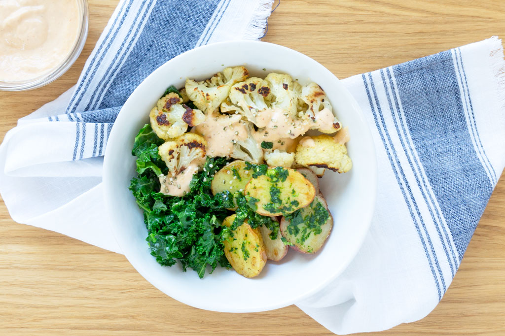 Vegan Buddha Bowls with cauliflower, kale, and potatoes overhead in a bowl
