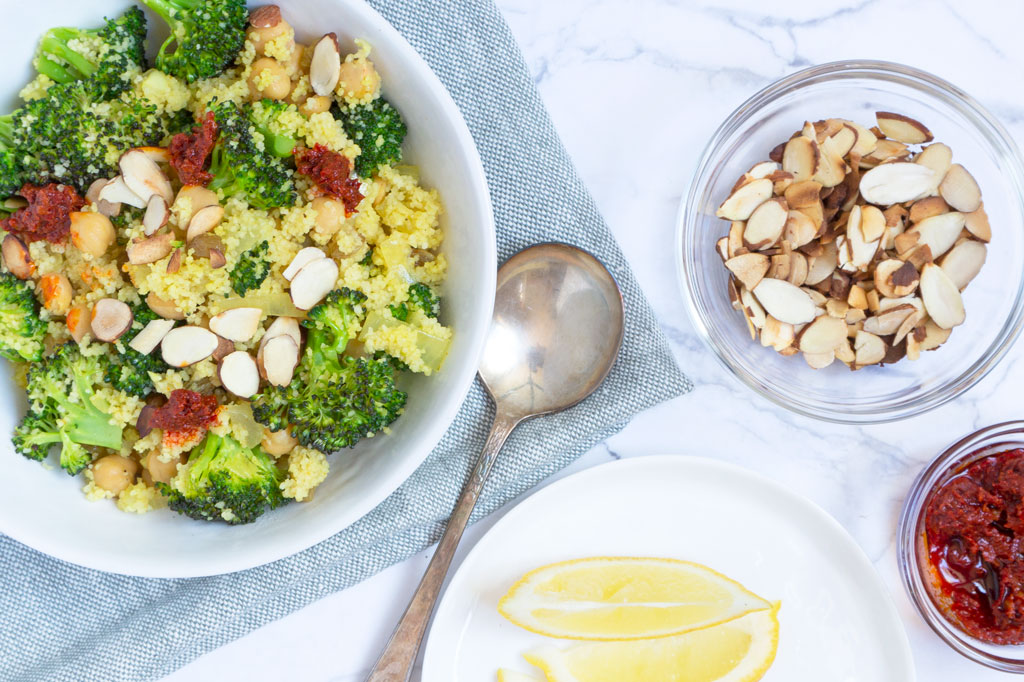 Vegan Broccoli Salad with Couscous with sliced lemons and bowl of harissa paste