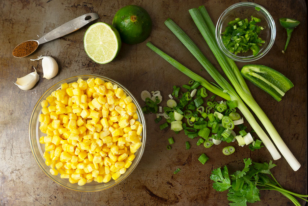 ingredients for elote - corn, garlic, lime, jalapeno, onion, chili powder
