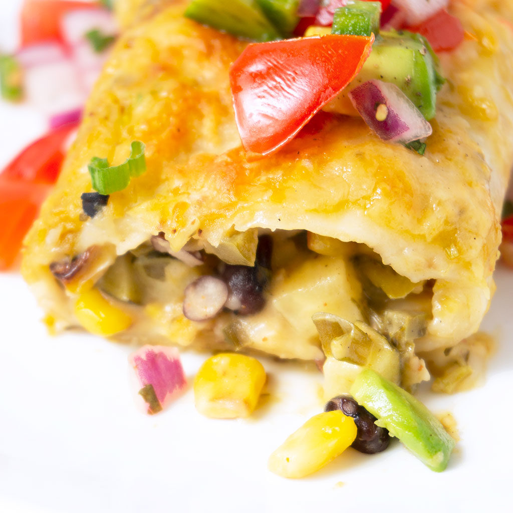 Close up of a zucchini enchiladas with tomatoes on top