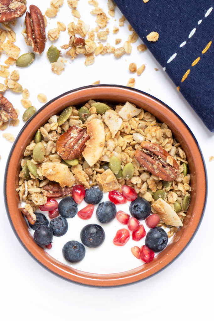 maple pecan granola with scattered pumpkin seeds, coconut chips and a blue napkin