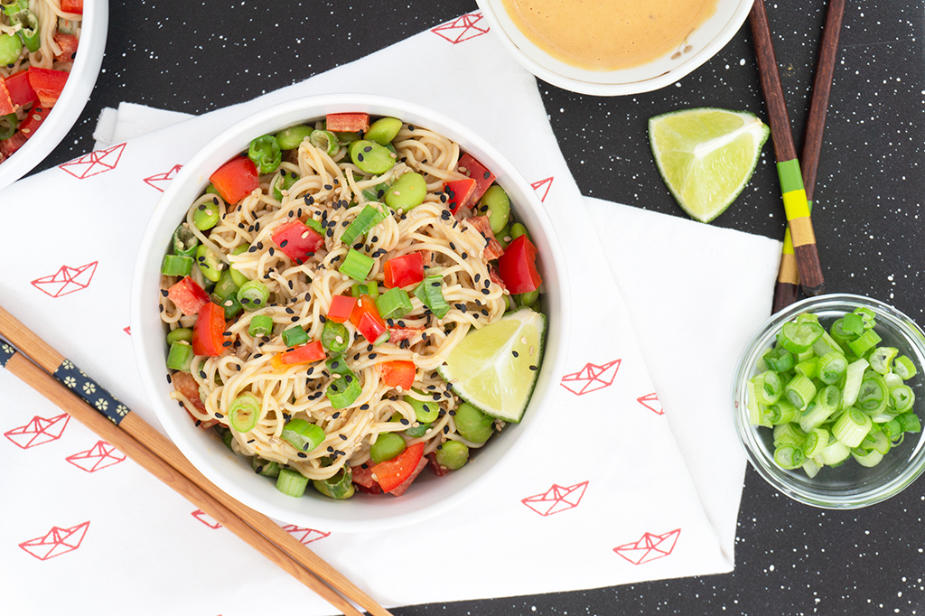 Tahini Noodle Bowl with red peppers and edamame on top overhead view