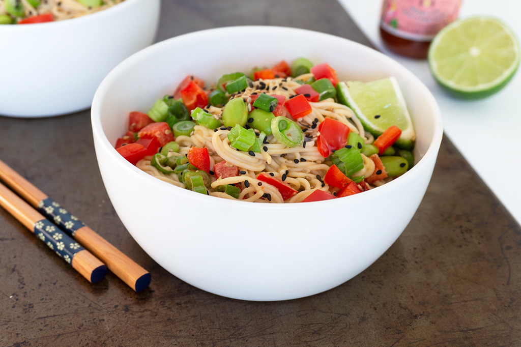 Tahini Noodle Bowl with red peppers and edamame on top and chopsticks